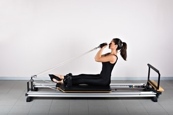 woman doing seated bicep curl pilates exercises on reformer